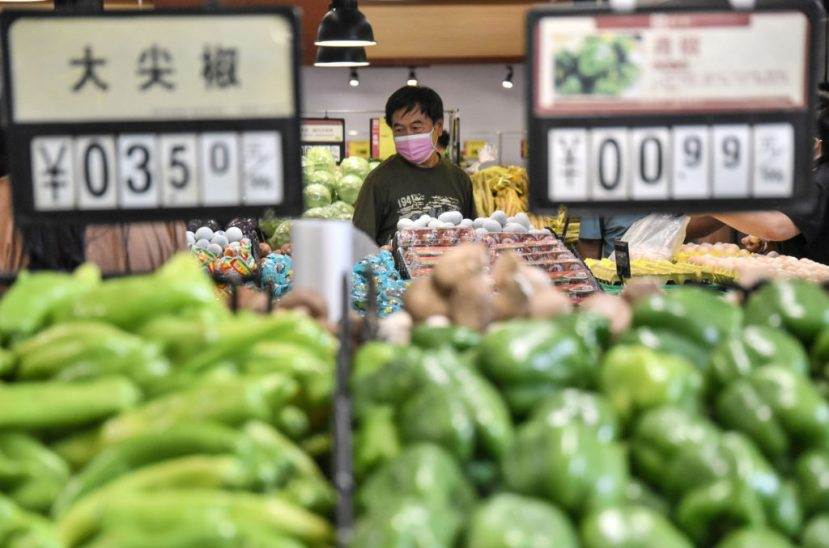 A customer buys vegetables at a supermarket in Handan in China's northern Hebei province on August 10, 2020.