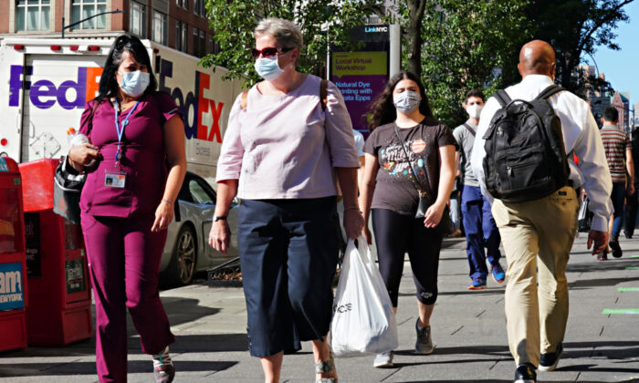 People walk while wearing protective masks as New York City moves into Phase 3 of reopening following restrictions imposed to curb the CCP virus pandemic, on July 14, 2020.