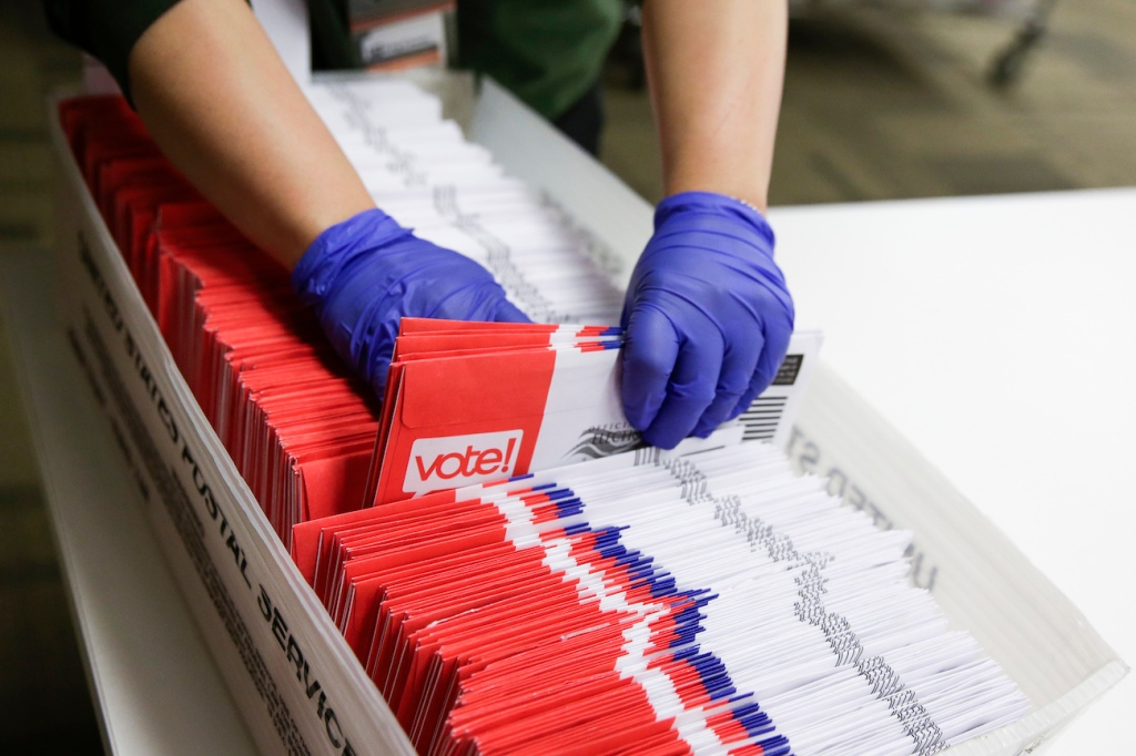 Election workers sort vote-by-mail ballots for the presidential primary at King County Elections in Renton, Wash., on March 10, 2020.