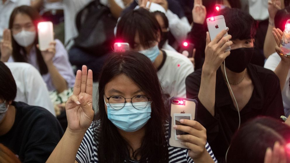 Pro-democracy students raise a three-finger symbol of resistance salute and hold mobile phones with flashlights switched on†during a protest at Chulalongkorn University in Bangkok, Thailand, Friday, Aug, 14, 2020.