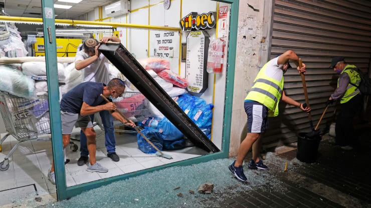 Israeli men remove the shattered glass window of a laundry shop following a rocket attack fired from the Gaza Strip and crashed in the southern coastal city of Ashdod on September 15, 2020.