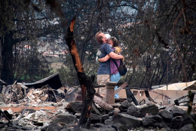 Dee Perez comforts Michael Reynolds in the ruins of his home destroyed in the Almeda Fire in Talent, Oregon.