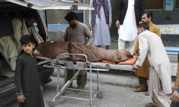 The body of a woman is taken away from the Jalalabad stadium on Wednesday.
