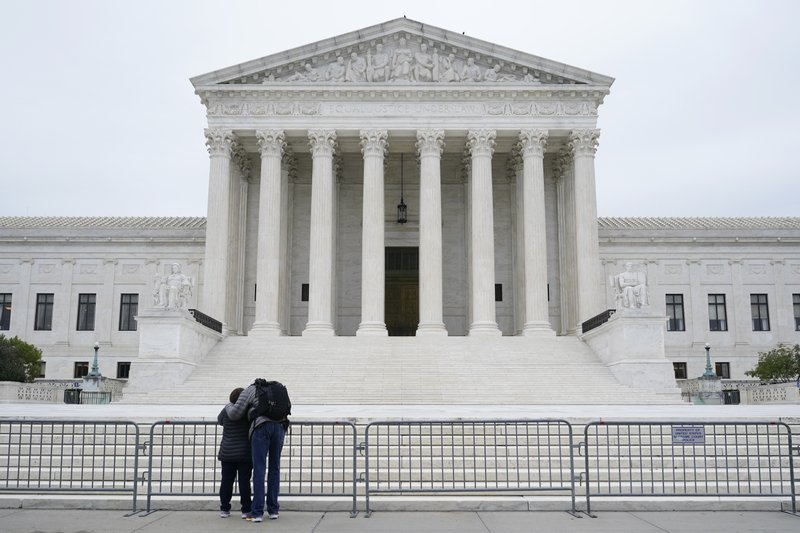 A woman and man pray outside the Supreme Court on Capitol Hill in Washington, Tuesday, Oct. 27, 2020, the day after the Senate confirmed Amy Coney Barrett to become a Supreme Court Justice.