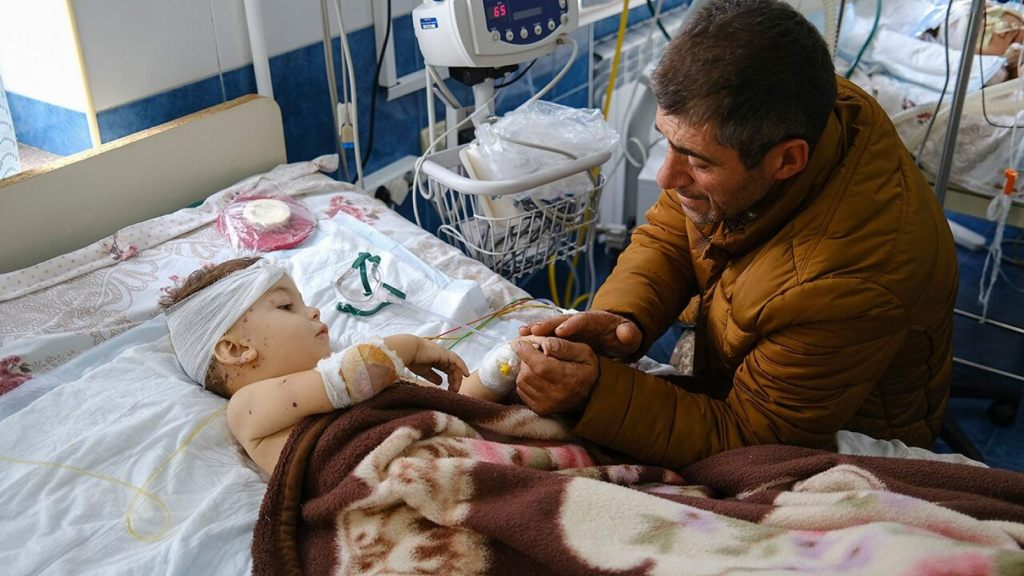 A man speaks with his child, wounded during shelling, in Stepanakert, the self-proclaimed Republic of Nagorno-Karabakh, Azerbaijan, Monday, Sept. 28, 2020.