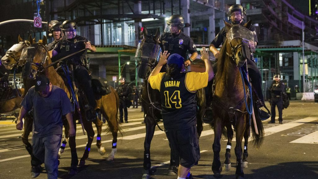 Police on horseback move people back as rowdy fans celebrate, Sunday, Oct. 11, 2020, in Los Angeles, after the Los Angeles Lakers defeated the Miami Heat in Game 6 of basketball's NBA Finals to win the championship.