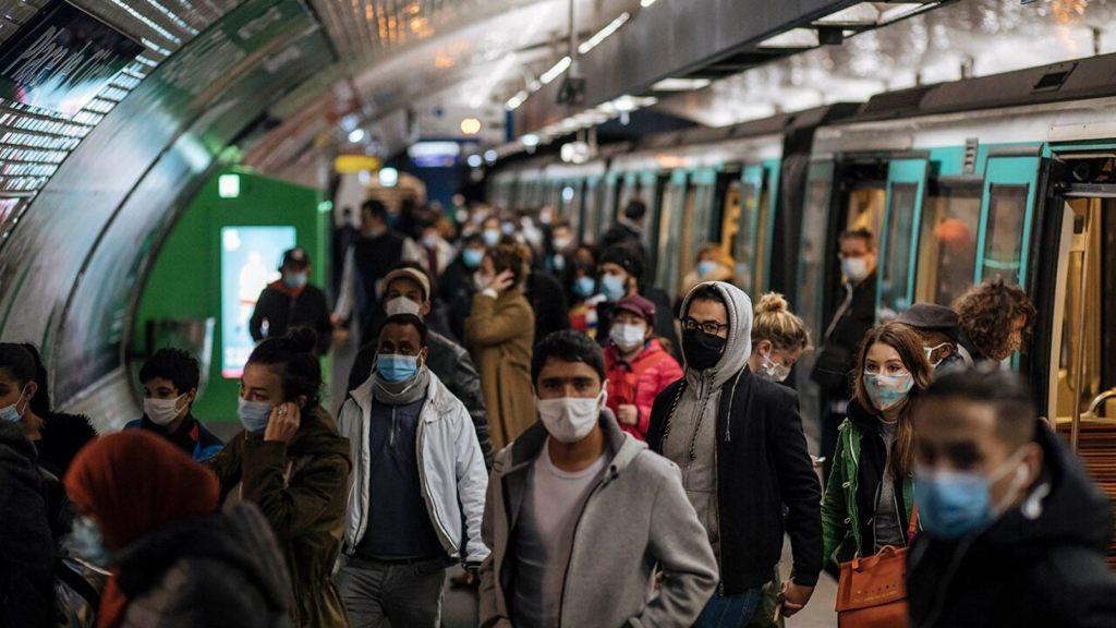 Commuters wearing face masks walk on the platform, of a Paris subway, Sunday Oct.25, 2020.