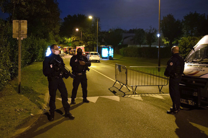 French police officers stand guard on a street in Eragny where an attacker was shot dead by policemen after he decapitated a man today.
