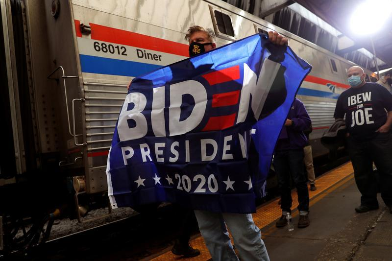 FILE PHOTO: A supporter of U.S. Democratic presidential candidate and former Vice President Joe Biden holds a flag as he stands next to Biden's campaign train during a campaign stop in Pittsburgh, Pennsylvania, U.S., September 30, 2020.