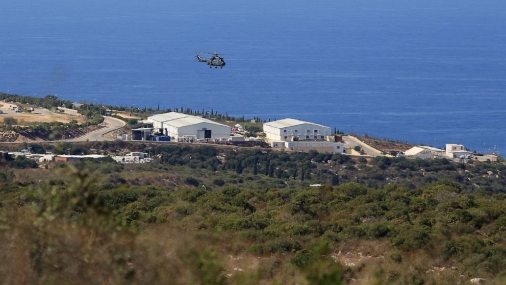 FILE - In this Oct. 14, 2020 file photo, a helicopter flies over a base of the U.N. peacekeeping force, in the southern town of Naqoura, Lebanon.