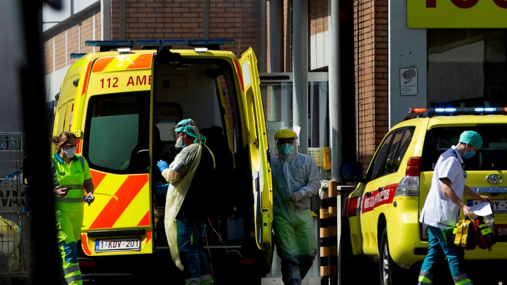 FILE - In this Monday, April 13, 2020 file photo, medical personnel in protective gear prepare to receive a patient at a hospital in Antwerp, Belgium.