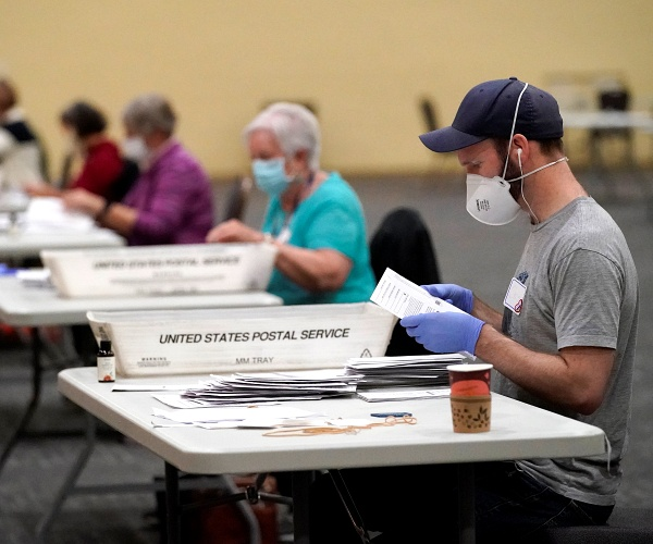 Workers prepare main-in ballots for counting, Wednesday, Nov. 4, 2020, at the convention center in Lancaster, Pa., following Tuesday's election.