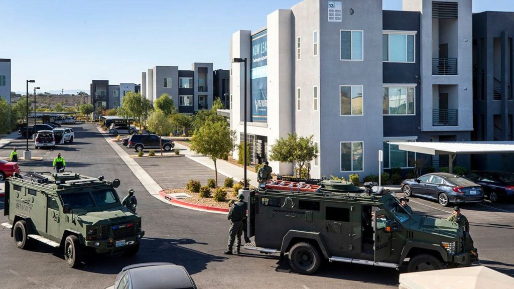 Henderson Police officers and SWAT vehicles are shown at the scene of a fatal shooting in an apartment complex in Henderson, Nevada. Four people were killed including the suspect in the shooting, police said.