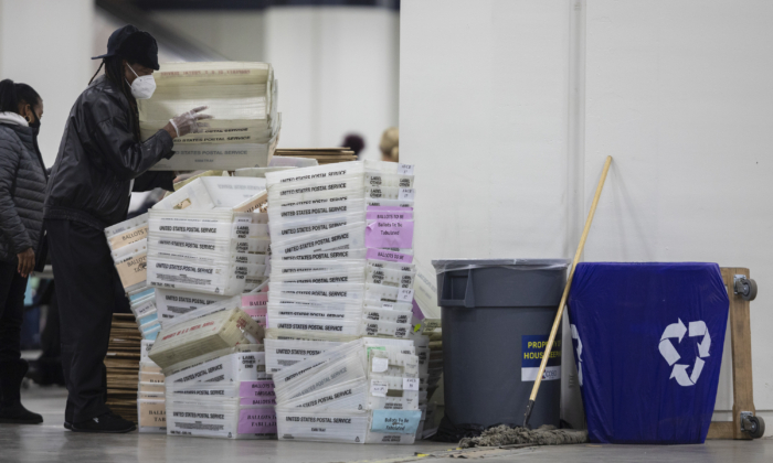 A worker with the Detroit Department of Elections helps stack empty boxes used to organize absentee ballots after nearing the end of the absentee ballot count at the Central Counting Board in the TCF Center in Detroit, Mich., on Nov. 4, 2020.
