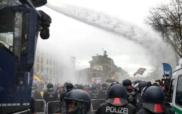 Police uses water canons to clear a blocked a road between the Brandenburg Gate and the Reichstag building, home of the German federal parliament,