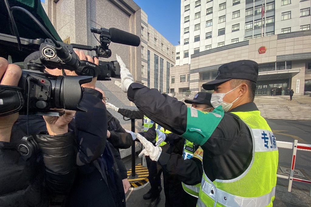 A policeman covers a camera to stop journalists from recording footage outside the Shanghai Pudong New District People's Court, where Chinese citizen journalist Zhang Zhan – who reported on Wuhan's Covid-19 outbreak and placed under detention since May – is set for trial in Shanghai on December 28,