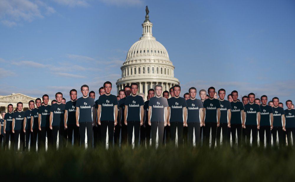 "FILE - In this April 10, 2018, file photo, life-sized cutouts depicting Facebook CEO Mark Zuckerberg wearing ""Fix Fakebook"" T-shirts are displayed by advocacy group, Avaaz, on the South East Lawn of the Capitol on Capitol Hill in Washington, ahead of Zuckerberg's appearance before a Senate Judiciary and Commerce Committees joint hearing. Federal regulators asked Wednesday, Dec. 9, 2020,"