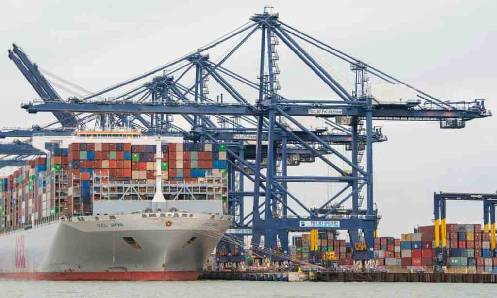 Shipping containers are unloaded from a cargo ship at the port of Felixstowe in Suffolk.