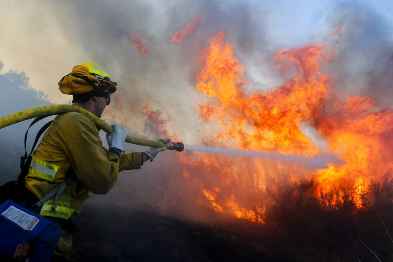 A firefighter battles the Bond Fire in Silverado, Calif., Thursday, Dec. 3,