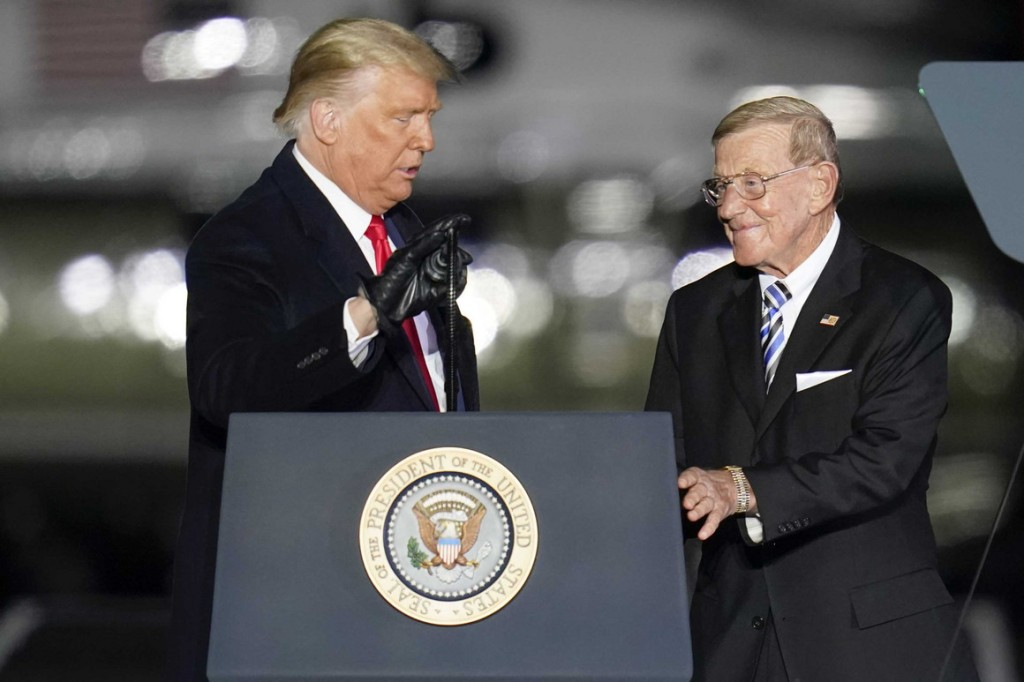 President Donald Trump, left, introduces former college football coach Lou Holtz during a campaign stop at the Butler County Regional Airport in Butler, Pa.