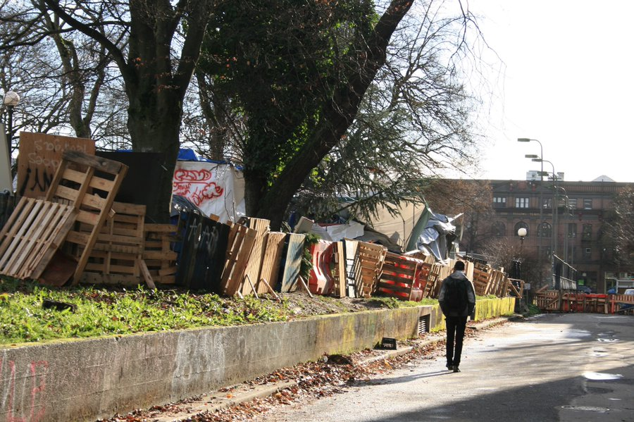 Man walks by barricades surrounding homeless encampment on Nagle Pl. Seattle,