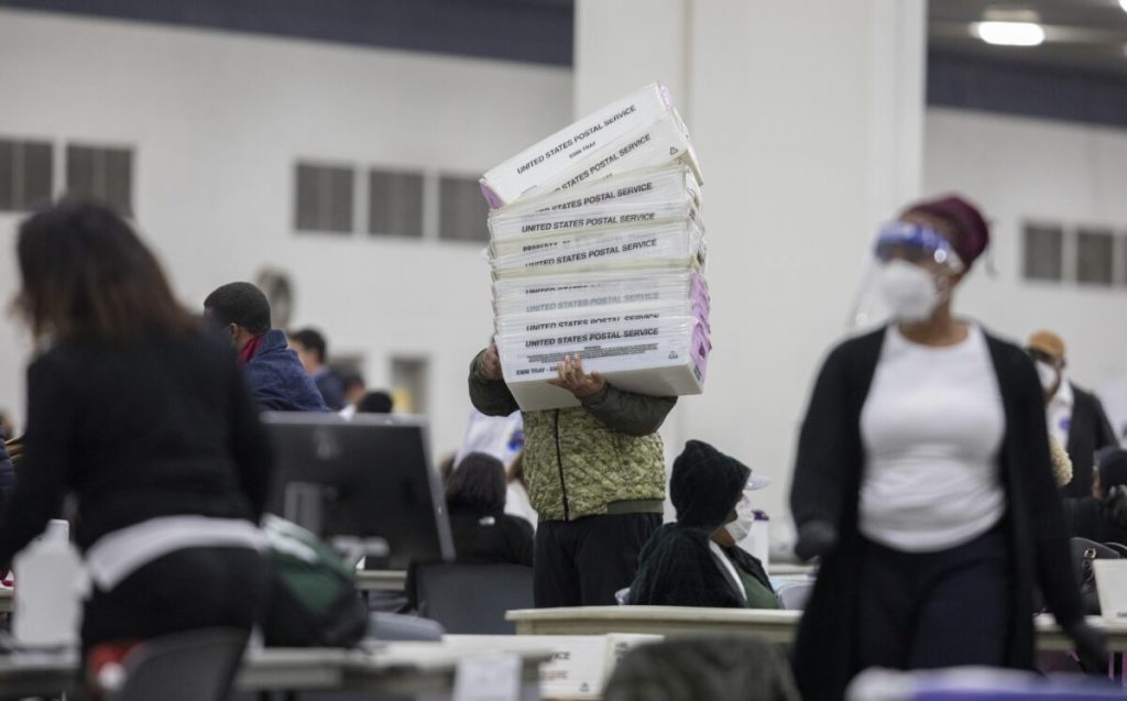 A worker with the Detroit Department of Elections carries empty boxes used to organize absentee ballots after nearing the end of the absentee ballot count,