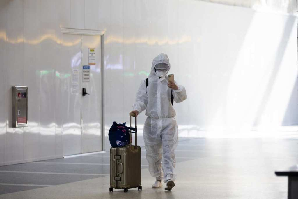 A passenger wearing personal protective equipment walks though Tom Bradley International Terminal at LAX in November 2020.