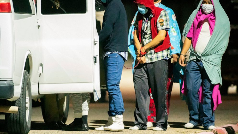 People are handcuffed together in pairs and loaded into vans as police investigate a possible human smuggling operation, Thursday night, Dec. 4, 2020, in Houston.