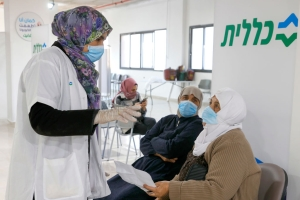 A healthcare worker speaks to an Arab Israeli woman before giving her a COVID-19 vaccine at Clalit Health Services, in the Arab city of Umm al Fahm, Israel on January 4, 2021.