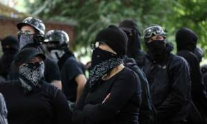 File – Antifa members gather at a rally in Portland, Ore., on Saturday, June 30, 2018.