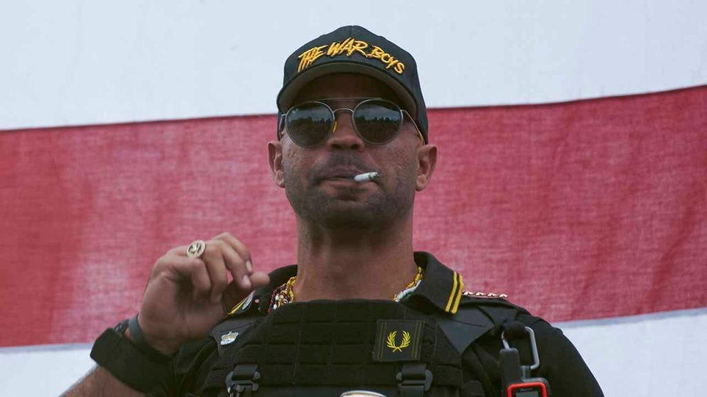 """In this Sept. 26, 2020, file photo, Proud Boys leader Henry """"Enrique"""" Tarrio wears a hat that says The War Boys during a rally in Portland,"""