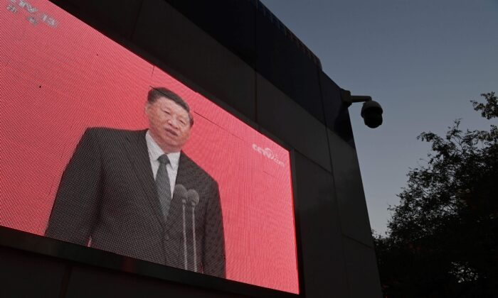 A video clip of Chinese Leader Xi Jinping is seen on the outside of a police patrol station in Beijing on Nov. 2, 2020.