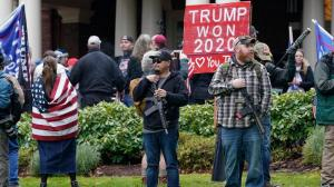 Supporters of President Trump, including those with guns and a bat, stand outside the Governor's Mansion after breaching a perimeter fence, Wednesday, Jan. 6, 2021, at the Capitol in Olympia, Wash.