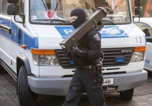 A police walks in front of a car during raids against an Islamist network at the Maerkische Viertel neighborhood in Berlin, Thursday, Feb. 25, 2021. Police searched the apartments of several alleged supporters of a banned Islamic extremist organization in the German capital.