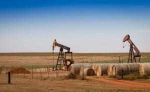Oil pumps and hay bales in rural Oklahoma.  Richard G Smith / Shutterstock.com