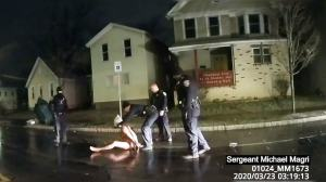 """In this image taken from police body camera video provided by Roth and Roth LLP on Sept. 2, 2020, a Rochester police officer puts a """"spit hood"""" over the head of Daniel Prude, on March 23, 2020, in Rochester, N.Y."""