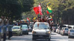 Buddhist religious and military flags are waved by supporters including Buddhist monks onboard a vehicle Monday, Feb. 1, 2021, in Yangon, Burma.