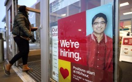 A passerby walks past an employment hiring sign while entering a Target store location in Westwood, Mass.