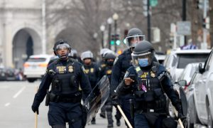 Police officers in riot gear walk towards the U.S. Capitol as a group protesters breached the Capitol building in Washington on Jan. 6, 2021.