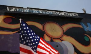 An American flag flies on a car next to a mural at Maywood Park in Maywood, Calif.,