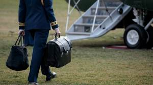 FILE - A military aide carries the alleged 'football,' a case with the launch codes for nuclear weapons, toward Marine One as former President Donald Trump prepares to take off.