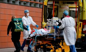 Medics take a patient from an ambulance into the Royal London hospital in London on Jan. 19, 2021.