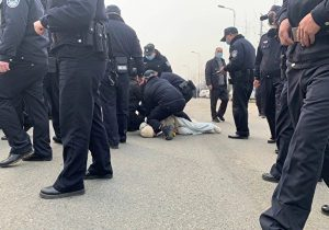 A female protester experiences overuse of force, with her neck pressured by the leg and knee of a policeman. Provided by an insider to The Epoch Times.