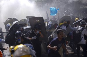 Protesters are dispersed as riot police fire tear gas during a demonstration in Yangon, Myanmar, Monday, March 8, 2021.