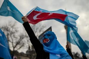 A protester from the Uyghur community living in Turkey waves a Turkish flag during a protest against the visit of China's Foreign Minister Wang Yi to Turkey, in Istanbul, Thursday, March 25, 2021.