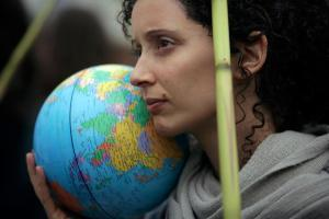 FILE- In this Nov. 29, 2019, file photo, a demonstrator holds a terrestrial globe in Lisbon during a worldwide protest demanding action on climate change.