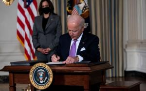 Vice President Kamala Harris looks on as U.S. President Joe Biden signs executives orders (Doug Mills-Pool / Getty Images)