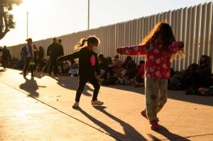 Children play as families of asylum seekers wait outside the El Chaparral border crossing port as they wait to cross into the United States in Tijuana, Baja California state, Mexico on February 19, 2021.