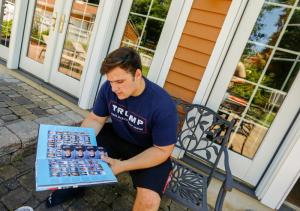 """In this June 9, 2017, file photo, Grant Berardo, a student at Wall High School, flips through his 2017 school yearbook in Wall, N.J. The yearbook includes a photo of him wearing a digitally altered T-shirt that originally included the words """"Trump Make America Great Again."""""""