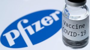 """A bottle reading """"COVID-19 Vaccine"""" is seen next to the Pfizer company logo in Paris, France, on Nov. 23, 2020. (Joel Saget/AFP via Getty Images)"""